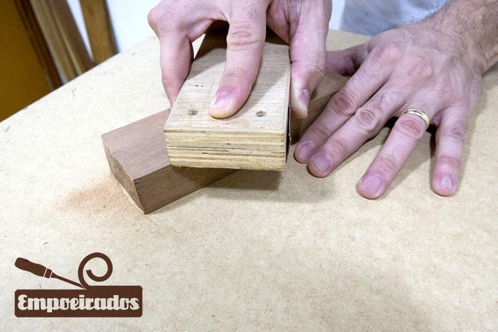 Lixando a madeira usando um taco de lixa